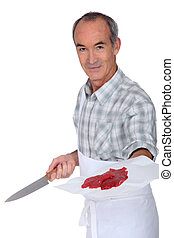 mature butcher with knife showing steak