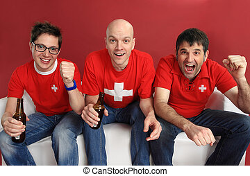 Cheering for the Swiss team - Photo of three male Swiss...