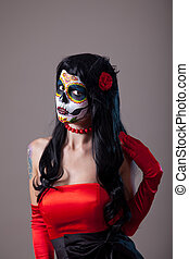 Woman with sugar skull make-up wearing red dress, the Day of...