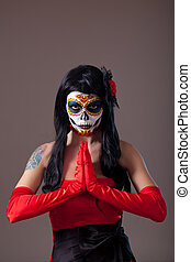 Praying woman with sugar skull make-up - Praying woman with...