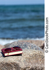 Closed Book with dark tinted sun glasses lies on a rock on the beach
