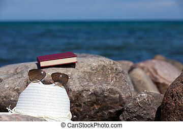 Closed Book with sun glasses and a straw hat lies on a rock on the beach