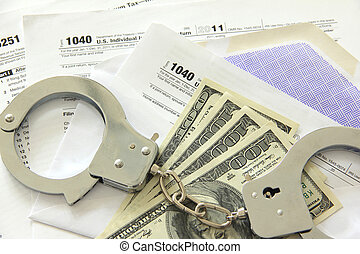 Tax papers with dollar bills and handcuffs - Tax papers in...