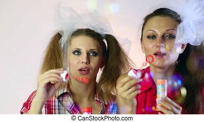 Soap bubbles. - Two young girls, pop bubbles