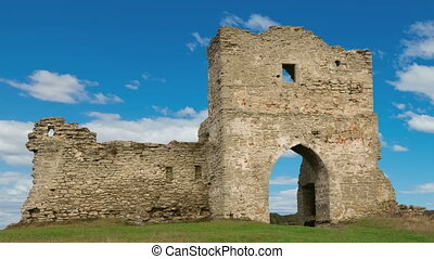 Ruined gates of cossack castle with blue sky and clouds