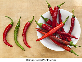 Three Chilis - 2 chili red peppers and a green one beside a...