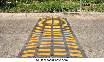 Speed bump on a road - Speed bump on a road when a car is...