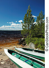 Two canoes left on a bank of lake - Two canoes left on a...
