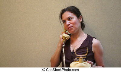 Woman on a Retro Style Telephone - Beautiful woman with a...