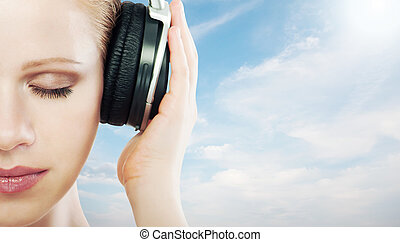 music concept. half of the face woman with headphones on the...