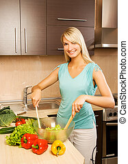 Beautiful young woman mixing vegetable salad in a glass bowl