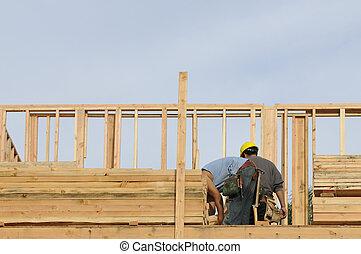 Carpenter picking up blocking - Hispanc construction worker...