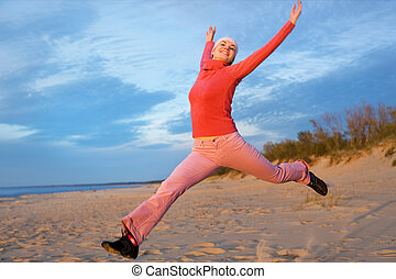 Beautiful young woman jumping on a beach