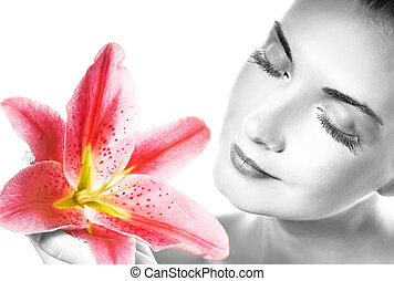 Beautiful young woman with pink lily close-up portrait....