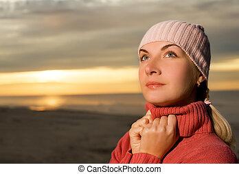Beautiful woman on a beach at sunset