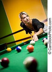 Beautiful blond woman playing billiards