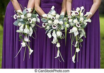 three bridesmaids holding wedding bouquets - three...