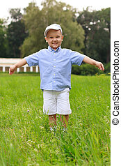 Smiling cheerful asian child in a cap and shorts in the park