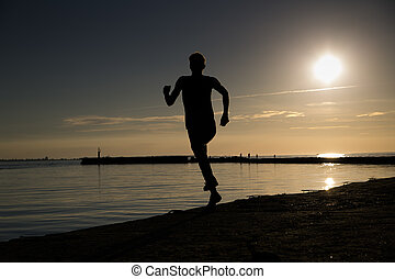Sportsman making jumpy movement at beach evening - Sportsman...