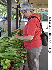 Woman at farmers market - corm - Woman looking at corn at...