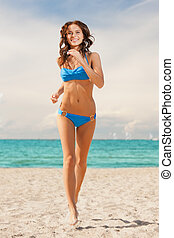 happy smiling woman jogging on the beach - picture of happy...