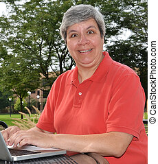 Happy middle-aged woman at laptop