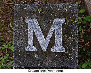 Block letter M in ground - Block with letter M stone, in...