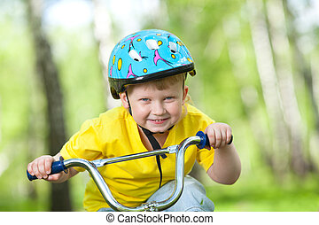 Portrait of a cute kid on bicycle