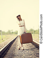 Young fashion girl with suitcase at railways.