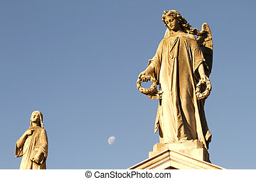 Statue in the Cemetery of Recoleta with the Moon in the background, Buenos Aires, Argentina.