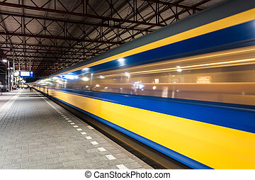 Train arriving in train station - Yellow and blue train...