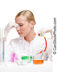 Tired female doctor is surrounded with medical glassware