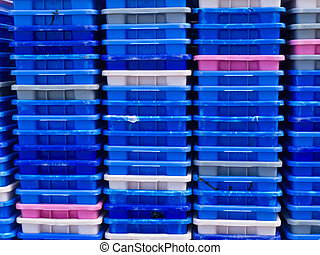 Stack of empty colorful plastic fishery containers -...