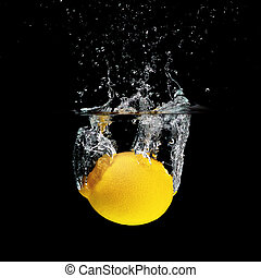 Lemon - Fresh lemon falling into water isolated on black...