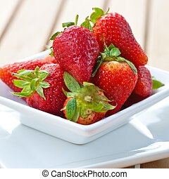 Delicious fresh ripened strawberries in a white bowl.