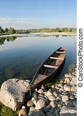 pirogue on a river - single rusty pirogue on Ticino River,...