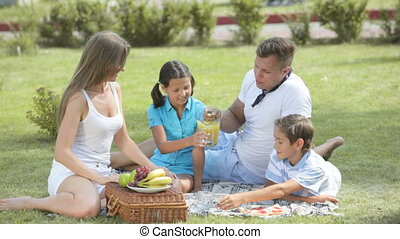 Family snack - Cheerful family sitting on the grass having a...