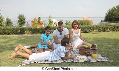 Yummy - Parents and kids hanging out together eating in the...