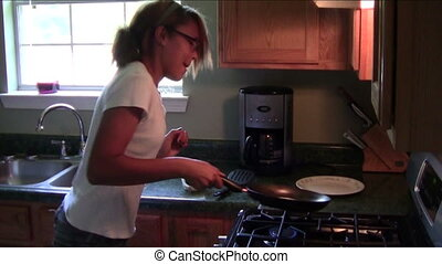 Pancake Flipping Practice - Teen girl practicing pancake...
