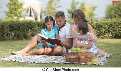 Summer fairy-tail - Father reading a book to his kids on a...