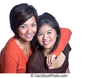 Two beautiful Asian sisters on white background