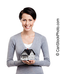 Holding small toy house in front of herself - Young woman...