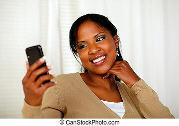 Friendly black woman sending a text message - Portrait of a...