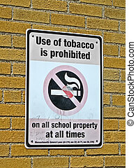 use of tabacco prohibited in all schools as message on sigbboard on brick wall, health details