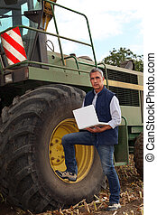 a farmer and his laptop near a combine harvester