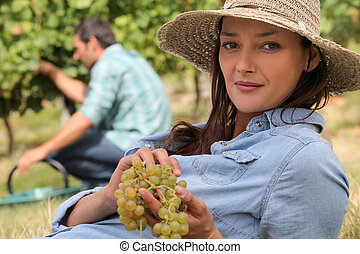 a woman wearing a straw hat is eating grapes behind a man...