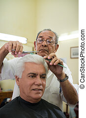 Old barber cutting hair to client in barber shop - Active...