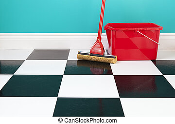 Mop and Bucket - A red bucket and mop on a white and black...