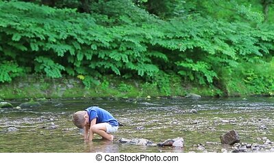Boy throws a stone into the river