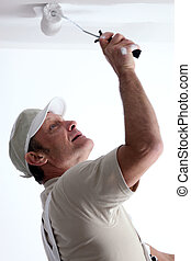 Man painting ceiling with a paint roller